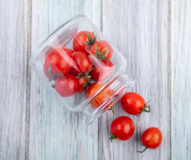 Top view of tomatoes spilling out of jar on wooden surface