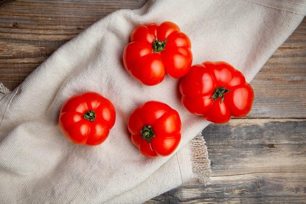 Pomodori di vista superiore sul panno bianco e sul fondo di legno scuro. orizzontale
