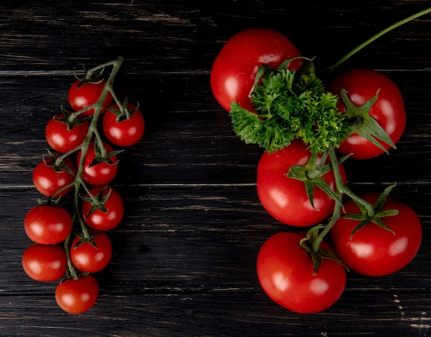 Top view of tomatoes with coriander on wooden surface