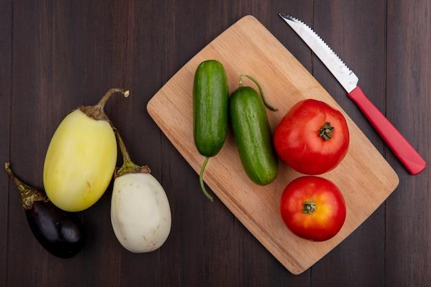 木製の背景のまな板にキュウリナスとナイフとトップビュートマト