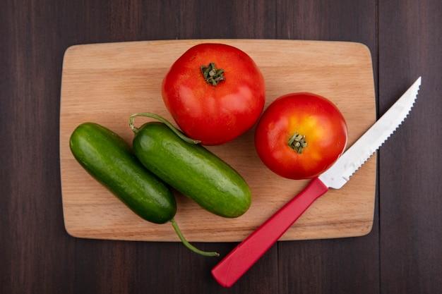 木製の背景のまな板にきゅうりとナイフとトップビュートマト
