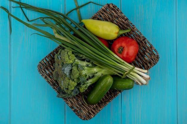 ターコイズブルーの背景のスタンドにきゅうりネギブロッコリーとピーマンとトップビュートマト