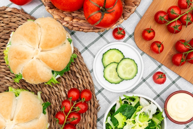 Top view of tomatoes with sandwiches and salad