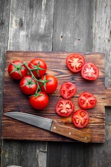 Pomodori di vista superiore con le fette in tagliere di legno con il coltello su fondo di legno scuro. verticale