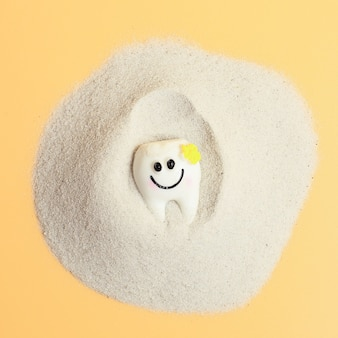 Top view tooth smiling on sand isolated on a yellow background