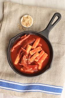 Top view 떡볶이 또는 떡볶이는 한국의 유명하고 인기 있는 길거리 음식인 참깨를 곁들인 매운 소스에 야채와 어묵을 볶은 떡입니다.