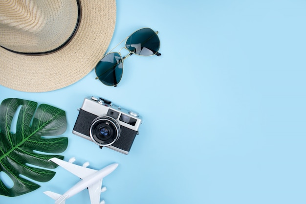 Top view of tourist accessories with film cameras, hats, sunglasses, smartphones and summer leaves on a blue background