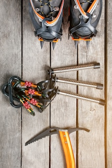 Top view of tourist equipment for a mountain trip on a rustic light wooden floor, sunlight