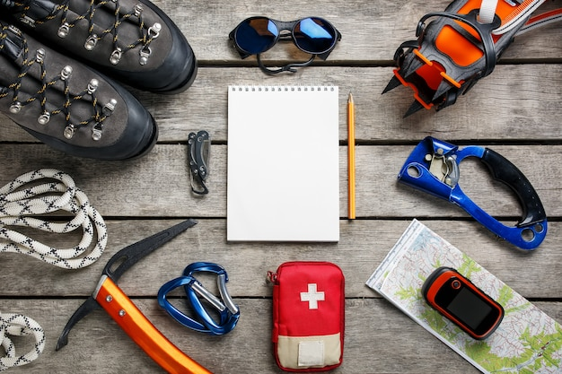 Top view of tourist equipment for a mountain trip on a rustic light wooden floor with a notebook