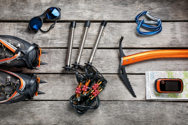 Top view of tourist equipment for a mountain trip on a rustic light wooden floor.