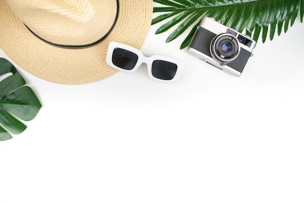 トップビュー、白い背景に麦わら帽子、フィルムカメラ、サングラス、夏の紅葉と観光機器。夏のアイテム。旅行 。