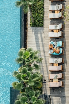 Top view of tourists sitting on outdoor chairs near swimming pool with palm trees in hotel area.