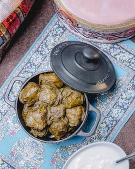 Vista dall'alto di un tradizionale dolma azero piatto in foglie di vite in una padella