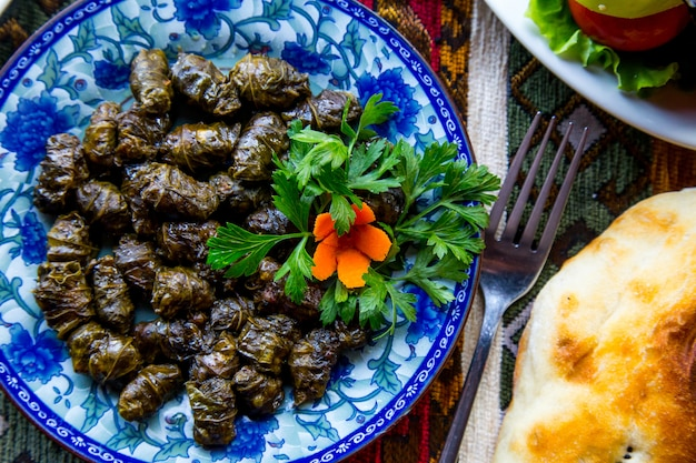 Vista dall'alto di un tradizionale piatto azero dolma carne in foglie di vite con prezzemolo e carotejpg