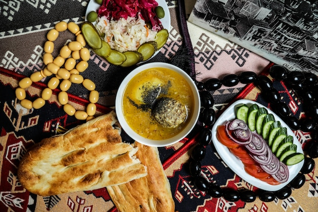 Vista dall'alto tradizionale piatto azero kyufta bozbash con pomodori cetrioli e cipolle con pane tandir sul tavolo