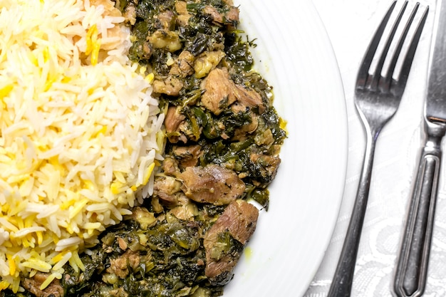 Top view a traditional azerbaijani dish syabzi pilaf fried meat with greens and boiled rice