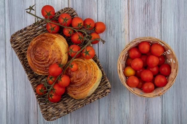 Vista dall'alto della tradizionale pasticceria azerbaigiana gogal su un vassoio di vimini con pomodori su un secchio su un grigio sfondo di legno