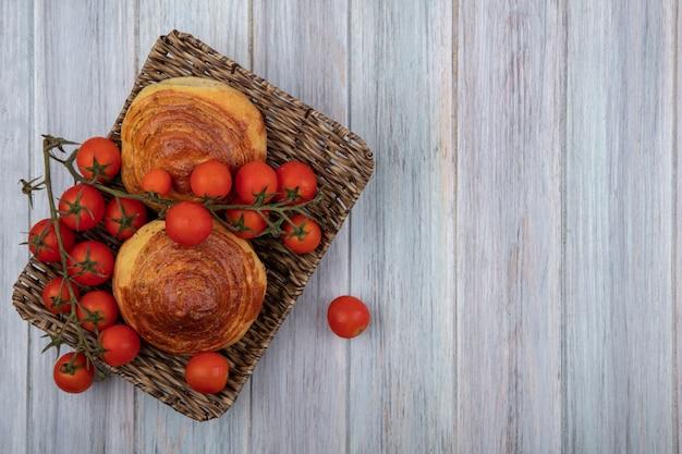 Vista dall'alto della tradizionale pasticceria azerbaigiana gogal su un vassoio di vimini con pomodori a grappolo su un grigio sfondo di legno con spazio di copia