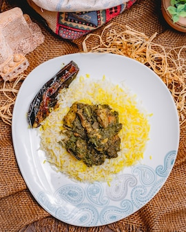 Top view traditional azerbaijani pilaf syabzi fried meat with greens and rice with eggplant