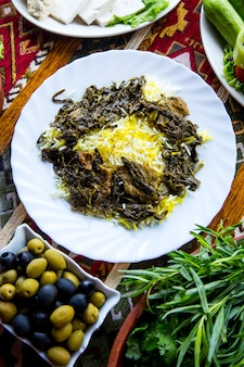 Top view traditional azerbaijani pilaf syabzi fried meat with greens and rice