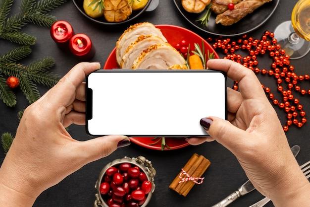 Vista dall'alto tradizionale disposizione di cucina natalizia con smartphone vuoto
