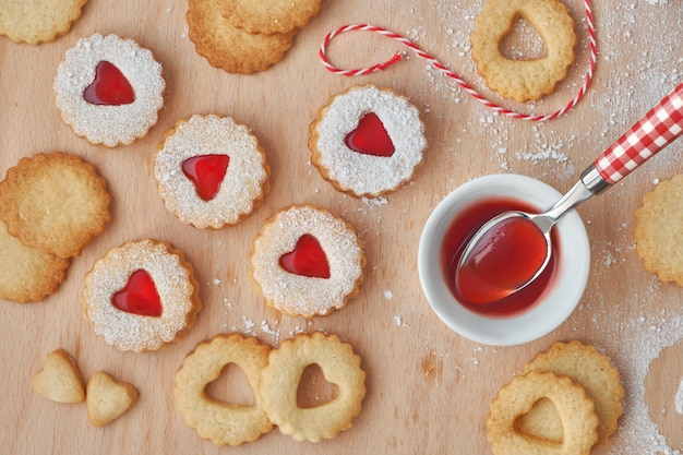 Top view of traditional christmas linzer cookies filled with strawberry jam on wooden board.