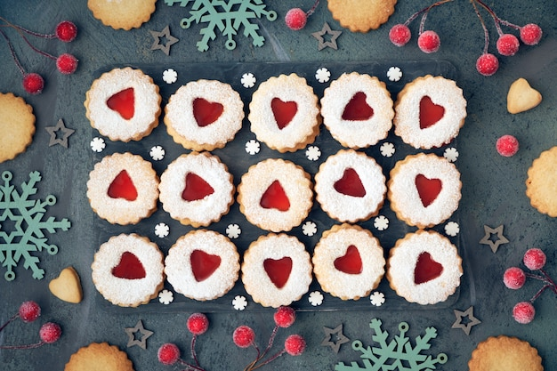 Top view of traditional christmas linzer cookies with red jam on dark