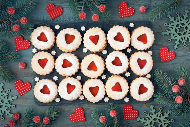 Top view of traditional christmas linzer cookies with red jam on rustic wood decorated with berries