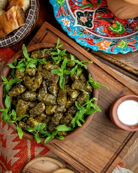 Top view of traditional dolma in grape leaves with sour yogurt on a wooden table