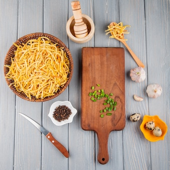 Top view of traditional homemade italian raw pasta in a wicker basket mortar wooden cutting board with chopped green onion and quail eggs on rustic background