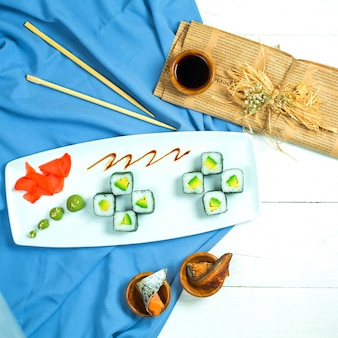 Top view of traditional japanese cuisine black sushi roll with rice avocado and cream cheese served with soy sauce ginger and wasabi on blue and white