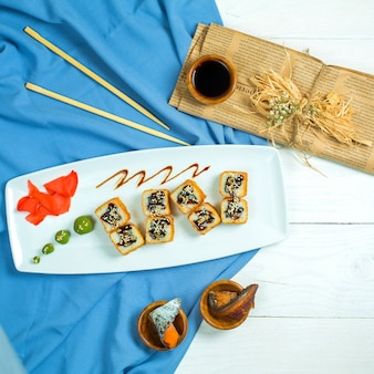 Top view of traditional japanese cuisine sushi roll with shrimps avocado and cream cheese on blue and white