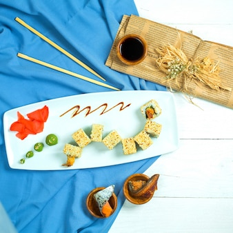 Top view of traditional japanese cuisine sushi rollwith rice shrimps avocado and cream cheese served with soy sauce ginger and wasabi on blue and white