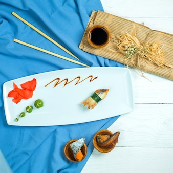 Top view of traditional japanese nigiri sushi with eel served with soy sauce and ginger with wasabi on blue and white