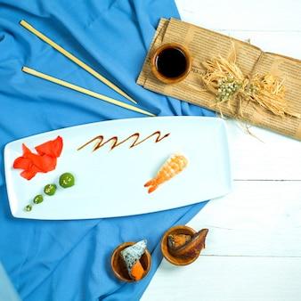 La vista superiore dei sushi giapponesi tradizionali di nigiri con gamberetto è servito con la salsa di soia e lo zenzero con wasabi su blu e su bianco