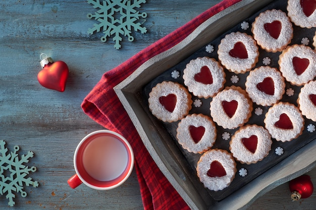 Top view of traditional linzer cookies with red jam heart on dar