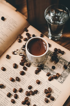 Top view traditional turkish coffee with coffee beans on an open book with a glass of water