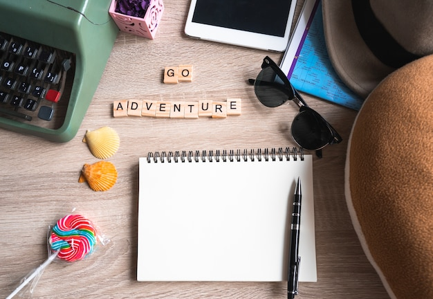 Top view travel accessories with blank book and go adventure words written on wooden block