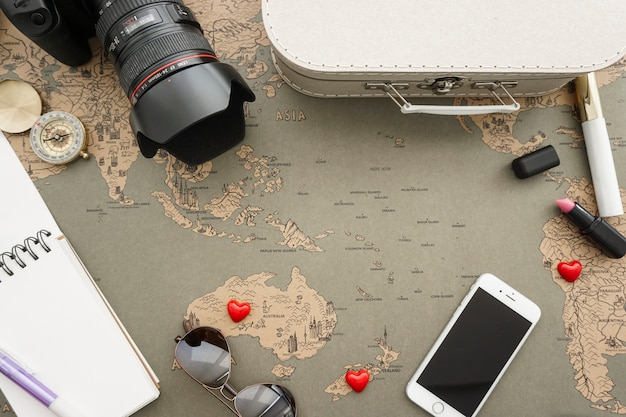Top view of travel accessories on world map
