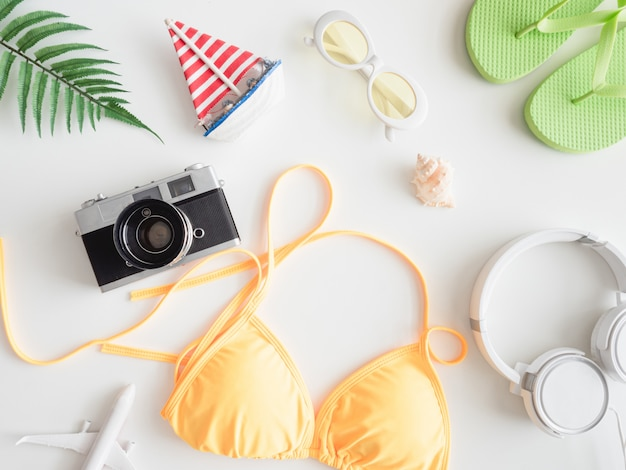 Top view travel concept with bikini, luggage and outfit of traveler on white wooden background, tourist essentials, vintage tone effect