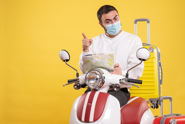 Top view of travel concept with confident guy in medical mask standing near motorcycle with yellow suitcase on it and holding map pointing forward