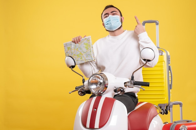 Top view of travel concept with confident guy in medical mask standing near motorcycle with yellow suitcase on it and holding map