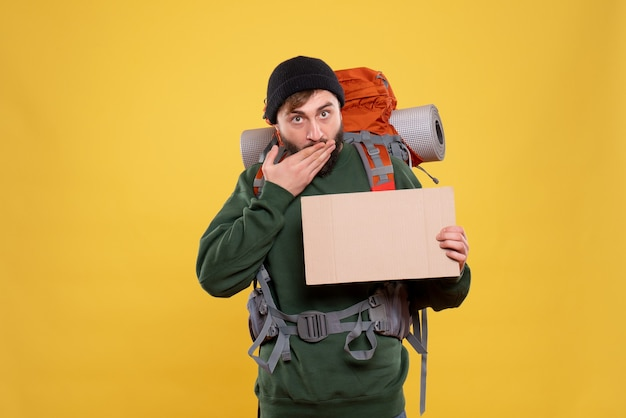 Top view of travel concept with confused young guy with packpack and holding free space for writing