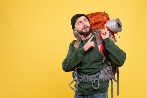 Top view of travel concept with curious young guy with packpack and pointing up