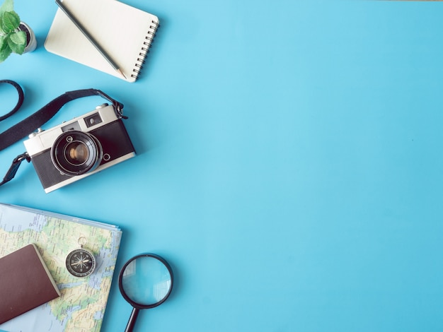 Top view travel concept with retro camera films, map, passport and compass on blue background with copy space, tourist essentials, vintage tone effect