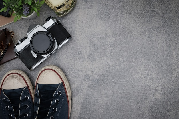 Top view travel concept with retro camera films,other items on grey cement background