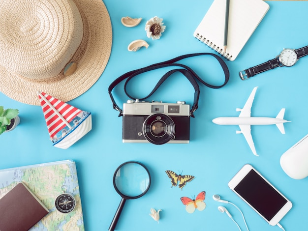 Top view travel concept with retro camera films, smartphone, map, passport, compass and outfit of traveler on blue background, tourist essentials, vintage tone effect
