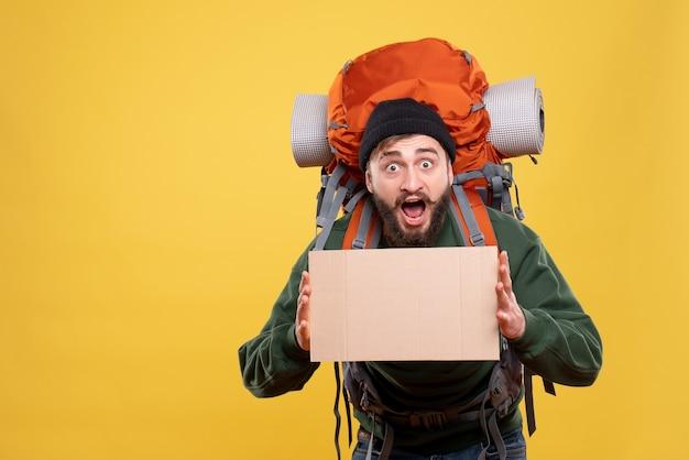 Vista dall'alto del concetto di viaggio con giovane ragazzo scioccato con packpack che tiene spazio libero per la scrittura