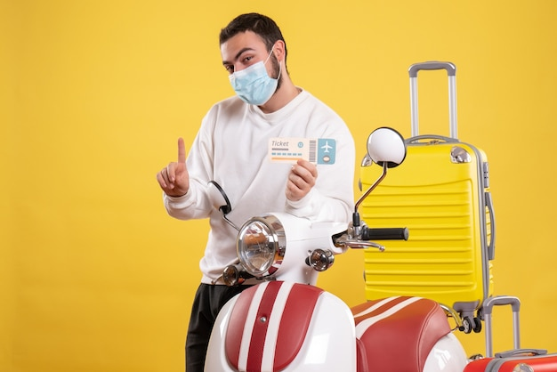 Top view of travel concept with smiling guy in medical mask standing near motorcycle with yellow suitcase on it and holding ticket pointing up