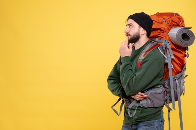 Top view of travel concept with thoughtful young guy with packpack